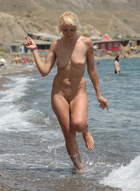 Nudist blonde running in the water